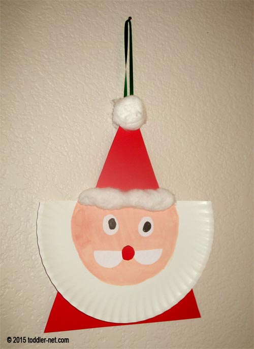 Paper plate Santa is hanging on the wall